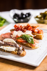 Tasty italian appetizer bruschettes with tomatoes anchovies prosciutto and mozarella