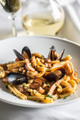 Italian pasta with mussels and prawn in white plate