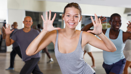 Group of active young woman and men practicing modern dance together