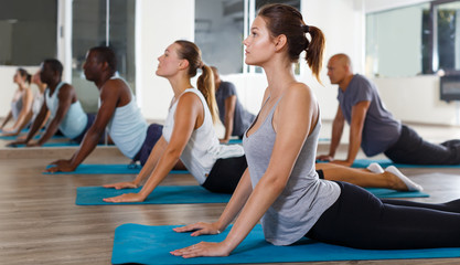 Glad women and men exercising during yoga class