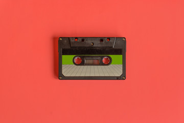 Audio cassette tape on pastel colored background. Retro style.