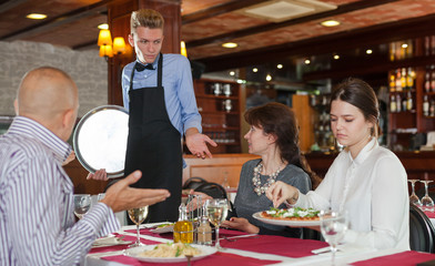 Dissatisfied guests complaining to waiter