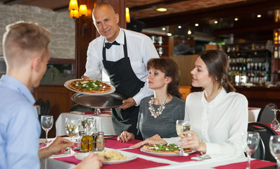 Waiter serving friendly company