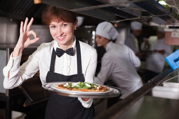 Smiling waitress with pizza in restaurant kitchen