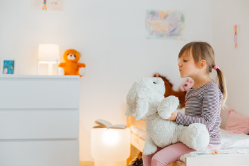 Little girl playing with soft toy