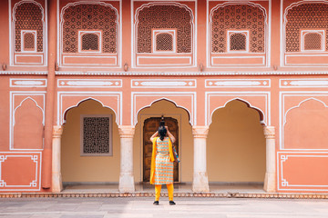City Palace, pink wall and woman in Jaipur, India
