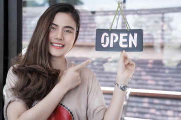 Young beautiful woman smiling and looking at camera white pointing at open sign
