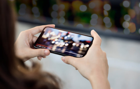 Cropped image of woman hand holding smartphone and watching video with night bokeh background.