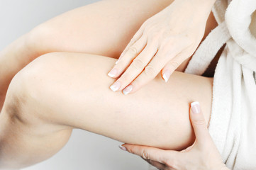 Female legs close up. Cosmetology and body care. Product for spa prodedur. Light background.