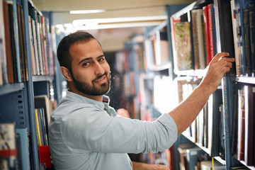 Adult Arabian bookseller picking out a book for customer standing between shelves in the bookshop