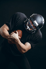 American football sportsman player in black helmet and uniform isolated over black background running in action