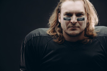 Portrait of confident fair-haired American football male player with war paint applied on his face looking at camera over black background