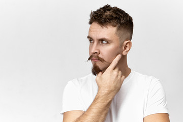 Attractive stylish young bearded guy with mustache thinking over something, holding hand on his face, posing against blank studio wall background with copy space for your advertising information