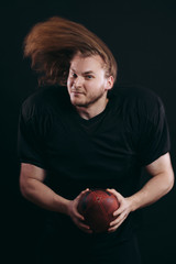Confident caucasian american football player in black protective uniform looking at camera, waving his hair on air, holding ball with both hands, being sure to win
