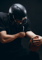 Caucasian athlete in american football player uniform and black helmet holding oval ball posing over black background