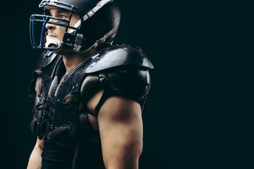 American football player with ball wearing helmet and protective shields isolated over black background