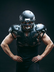 Portrait of sexy american football player wearing protective armour on shirtless torso, looking confidently, ready to tear apart everybody who bothers to win, isolated over dark studio background.