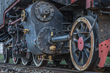 Old black steam locomotive train with close-up wheels and parts