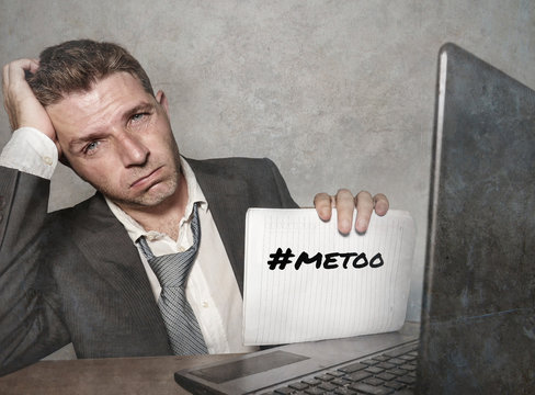 frustrated businessman desperate at office computer desk holding notepad with the hashtag me too metoo as exploited employee victim of mobbing and suffering abuse