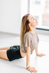 Young attractive woman with closed eyes practicing yoga,Ardha bhudjangasana. side view photo.close up shot.