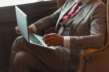 Senior bearded businessman in formal chic suit using laptop for work while sitting in big leather arm-chair in his office.