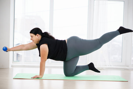 workout, fitness, active lifestyle, health. overweight woman doing isometric exercise during home workout