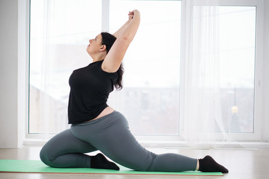 flexibility, grace, good mood, healthy lifestyle,vitality, yoga. pilates fat burning workout for women. overweight lady stretching in yoga studio