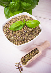 Fresh and dried basil on a wooden background.