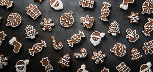 Panoramic view of many homemade gingerbread cookies on dark background