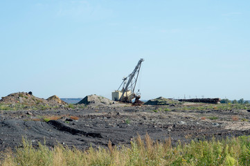 A huge excavator carries rock from the unloaded train from the mine. The concept of mining and environmental problems.