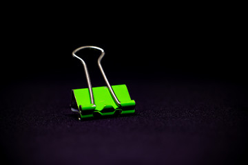 Green metal paper clip isolated on black background