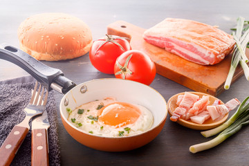 Fried egg in a pan, bacon, french fries tomatoes and green onions are cooked for breakfast on a wooden gray table. Close-up