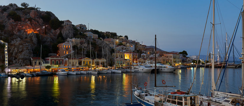 Symi Island Harbour view during the twillight.The colorful houses are illuminated by the lights