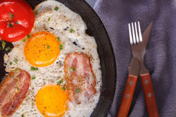 Fried eggs with bacon and tomatoes on an old cast iron pan and cutlery on a gray table. Close-up. Top view