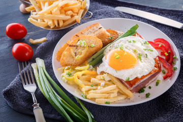 Fried egg with bacon in a white plate with fried pieces of bread, greens, tomatoes and french fries on a gray wooden table. Close-up