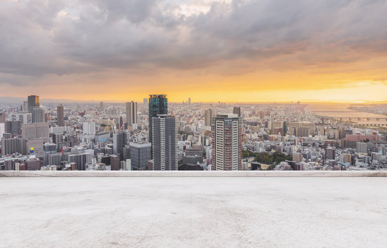 Osaka city skyline, downtown business district in sunset with empty concrete floor