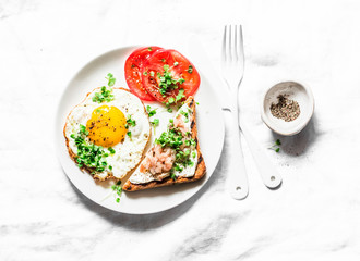 Breakfast served - fried egg, smoked mackerel cream cheese toast, tomatoes on a light background, top view