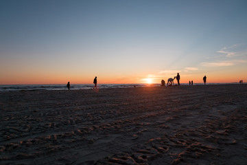 LIEPAJA, LATVIA - JULY 19, 2017: Walking people on the beach during sunset