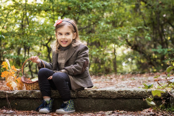 Autumn girl / Adorable little girl is walking through an autumn forest