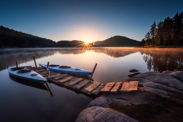 Lake sunrise / Beautiful sunrise view of mountain lake with  wooden bridge and canoes