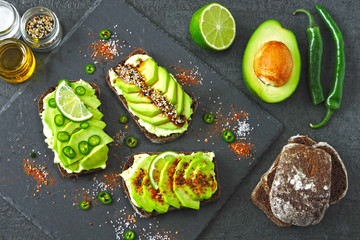 Rye avocado toast with chili and lime on a stone serving board. Healthy avocado toast. Top view. Flat lay.
