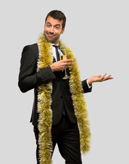 Man with champagne celebrating new year 2019 extending hands to the side for inviting to come on isolated grey background