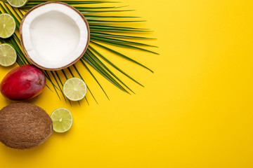 Tropical coconut, palm tree and fruits on yellow background