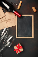Bottle of wine, two glasses, chalkboard, corkscrew and corks, on rusty background