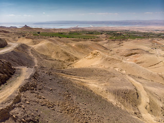 View over the Jordanian desert over the irrigated plantations and the saltworks at the Dead Sea with the coast of Israel in the haze, taken with the drone