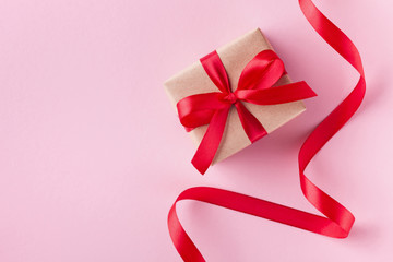 Gift box and red ribbon on pink pastel background for Valentines day card. Flat lay style.