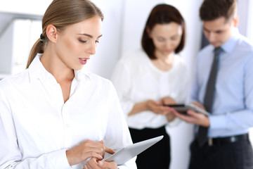 Beautiful blonde businesswoman standing straight in a brightly lit office at the background of colleagues or partners. Business concept