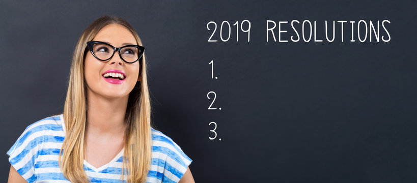 2019 Resolutions with happy young woman in front of a blackboard