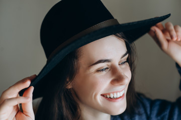 Portrait of beautiful young happy woman wearing  black hat .