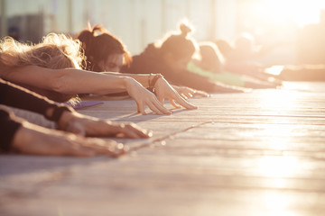 Child exercise, Balasana pose, working out. Yoga class. Group of sporty people doing yoga exercises in the morning at sunrise. Cropp shoot, sunny rays, healfy and calm concept, copy space